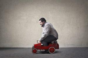 Mann fährt in zu kleinem Auto - es wirkt lächerlich und nicht kompetent