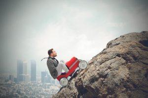 Mann in Seifenkiste auf dem Weg einen steilen Berg hinauf - er ist mit genügend Selbstbewusstsein und Selbstvertrauen ausgestattet