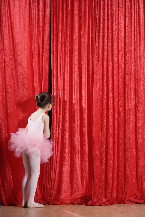 eine kleine Ballettänzerin schaut durch den roten Theatervorhang auf das Publikum - sie scheint großes Lampenfieber zu haben