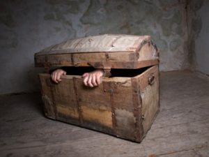 Ein Mensch sitzt in einer Kiste und hält von innen den Deckel zu.